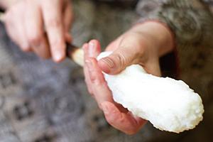 こねた米を串に巻きつけ、ぬらした手で形を整えていく