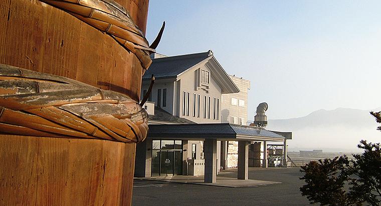 創業当時に使用していた50石入りの樽と現在の社屋